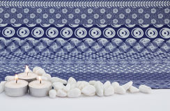 Three small white lit candles with white pebbles and indigo prin Royalty Free Stock Image