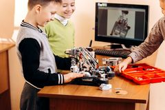 Three smart boys are making robots from the robotic constructor at the desk with computer in the School of Robotics royalty free stock photos
