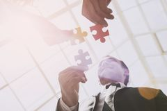 Three Smart Business Partners with Jigsaw Puzzles. Royalty Free Stock Photos
