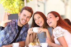 Three smiley friends taking selfies in a coffee shop stock photography