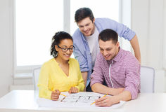 Three smiling architects working in office. Startup, education, architecture and office concept - three smiling architects with blueprint working in office Royalty Free Stock Photo