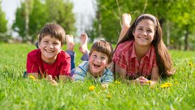 Three smiling kids lying together on green grass stock video footage