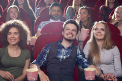 Three smiling best friends spending free time at cinema. stock photos