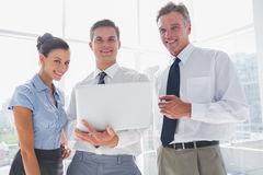 Three smiling business people holding a laptop Stock Photos