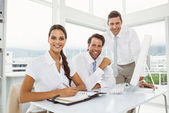 Three smiling business people at office desk Stock Photos