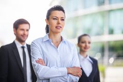 Three smiling business people standing outside. Royalty Free Stock Photos