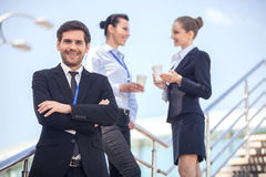 Three smiling business people standing on stairs. Stock Photos