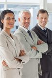 Three smiling business people standing together Stock Photo