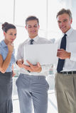 Three smiling business people using a laptop Stock Photography