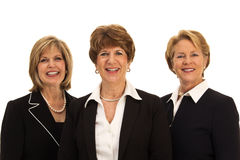 Three Smiling Business Women. Three mature women in business attire standing shoulder to shoulder, smiling open mouthed Royalty Free Stock Photos