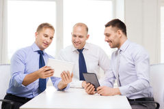 Three smiling businessmen with tablet pc in office Stock Image
