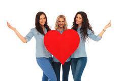 Three smiling casual women welcoming to their heart. On white studio background royalty free stock image