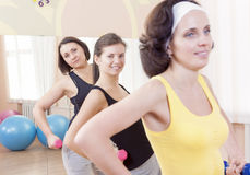 Three Smiling Caucasian Females Having a Workout Training with Barbells Indoors Stock Image