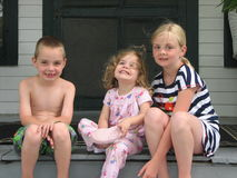 Three smiling children on front porch Royalty Free Stock Photos
