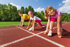 Three smiling children in ready position to run. Three smiling children in ready position on bending knee to run marathon in summer stock photo