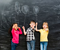 Three smiling children with thumbs up keeping imaginaru drawn balloons Royalty Free Stock Photography