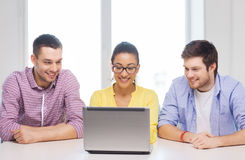 Three smiling colleagues with laptop in office Stock Images