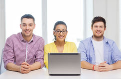 Three smiling colleagues with laptop in office Royalty Free Stock Image