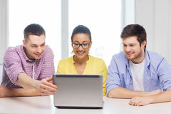 Three smiling colleagues with laptop in office Royalty Free Stock Photo