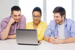 Three smiling colleagues with laptop in office Royalty Free Stock Images