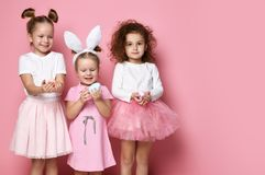 Three smiling dressed up for the holiday kid girls hold painted eggs on Easter day. Happy Easter celebration on pink background with free text space stock images