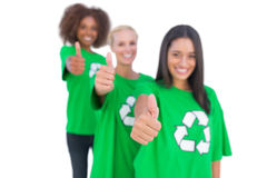 Three smiling enviromental activists giving thumbs up. In a line on white background Stock Photography