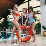 Three smiling female models posing in swimsuits with pineapples and lifebuoy ring at swimming-pool in luxurious hotel Stock Images