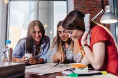 Three smiling female students learning together in classroom royalty free stock image