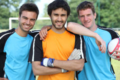 Three smiling footballers Stock Photos