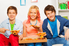 Three smiling friends hold pizza pieces and eat Stock Images