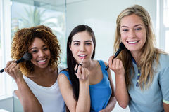 Three smiling friends putting makeup on together. In the bathroom Royalty Free Stock Image
