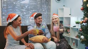 Three smiling friends in Santa hats making cheers with cocktails. There are skyscrapers in the background. Friends happiness concept stock video footage