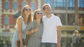 Three Smiling Friends Spending Time Together Outdoors During Warm Summer Day. Man Wearing White Shirt is Standing at the. Three Smiling Friends Spending Time stock video footage