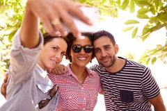 Three smiling friends taking a selfie stock image