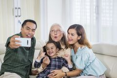 Three smiling generation family takes selfie at home stock photography
