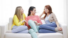 Three smiling girlfriends having a talk at home stock footage