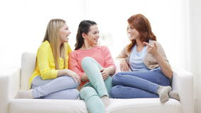 Three smiling girlfriends having a talk at home Royalty Free Stock Images