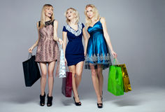Three smiling girls. Three beautiful happy blonde women shopping, posing with bags. Studio shot Stock Image