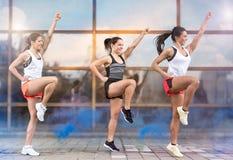 Three smiling girls doing aerobic exercises outside. Three athletic girls doing aerobic exercises outside stock photos