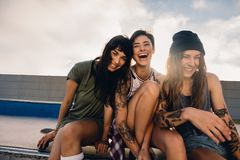 Three smiling girls hanging out at skate park Royalty Free Stock Photos