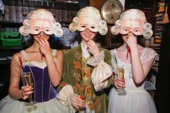 Three smiling girls in medieval costumes and masquerade masks are making fun at the backstage of the Bolshoy Theater. Moscow, Russia - April 2, 2006: Three royalty free stock image
