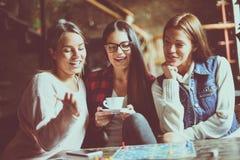 Three smiling girls playing board game. stock photos
