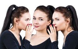 Three smiling girls whispering gossip Stock Image
