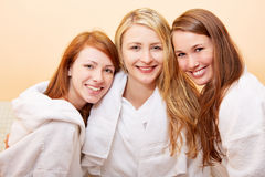 Three smiling happy attractive. Group of three smiling happy attractive women in bathrobe Royalty Free Stock Images