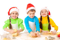 Three smiling kids with Christmas cooking stock photography