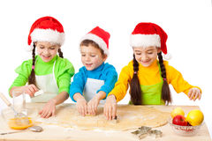 Three smiling kids with Christmas cooking Stock Images