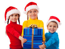Three smiling kids with Christmas gift Royalty Free Stock Photo