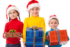 Three smiling kids with Christmas gift boxes Stock Photos