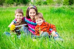 Three smiling kids on green meadow Stock Photos