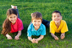 Three smiling kids on the meadow royalty free stock photography